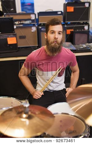 music, sale, people, musical instruments and entertainment concept - male musician playing cymbals at music store