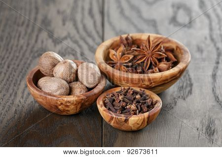 anise stars cloves and nutmeg in olive bowl on oak table, rustic