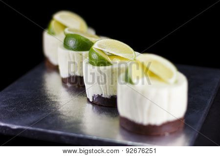 Four small cakes decorated with lime wedges