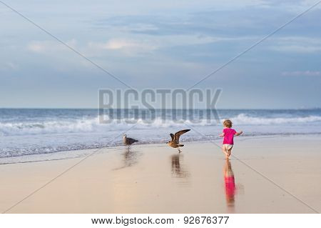 Adorable Curly Baby Girl Wearing A Diaper And Pink Shirt Running On A Beautiful Beach