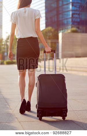 travel business woman pulling suitcase bag walking along sidewalk outdoors in urban city