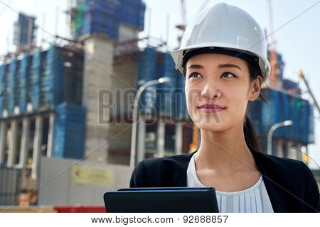 professional asian chinese business woman supervising construction site with hard hat protection at work