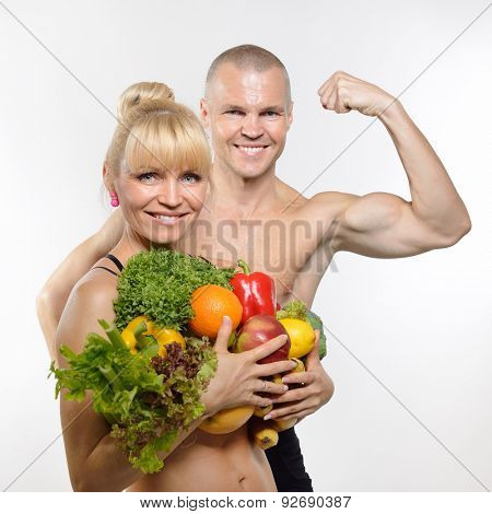 Attractive happy middle-age fit man and woman holding fruit and vegetables. Healthy eating, fitness, diet, vegetarianism and rawfoodist concept.