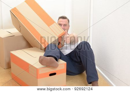 Man Moving Home Relaxing Amongst Boxes