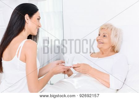 Pretty woman giving to her grandmother cup of tea.