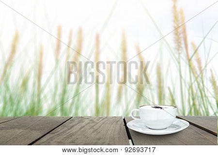 Fresh Green Grass In Beautiful Meadow And Coffee Cup On Veranda