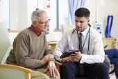 stock photo of chemotherapy  - Man Having Chemotherapy With Doctor Using Digital Tablet - JPG