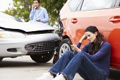 stock photo of driver  - Female Driver Making Phone Call After Traffic Accident - JPG