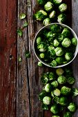 foto of brussels sprouts  - Top view of organic brussel sprouts in a white bowl on rustic wooden table - JPG