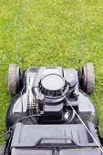 stock photo of grass-cutter  - top view of lawn mower on green grass - JPG