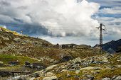 picture of italian alps  - High voltage electrical power line in the italian Alps in scenic high mountain landscape and dramatic stormy sky - JPG