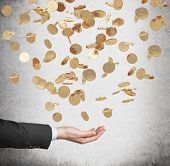 stock photo of golden coin  - Close up of the open palm and falling golden dollar coins from the ceiling - JPG