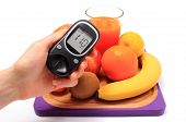 picture of immune  - Hand with glucose meter fresh ripe natural fruits and glass of juice on cutting board concept for diabetes healthy nutrition and strengthening immunity - JPG
