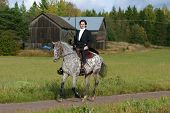 stock photo of appaloosa  - A man in tuxedo riding appaloosa mare with western tack - JPG