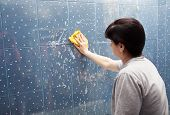 picture of soapy  - woman in a gray shirt washes blue tile with a cloth with soapy foam in the bathroom - JPG