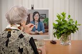 pic of telecommuting  - Senior woman taking a pill in front of virtual doctor - JPG