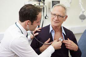 foto of hospital  - Doctor Examining Senior Male Patient In Hospital - JPG