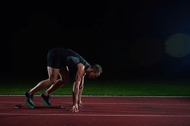 picture of sprinters  - Sprinter leaving starting blocks on the running track - JPG