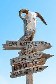 image of western nebraska  - Western signpost with goat skull to famous US landmarks - JPG