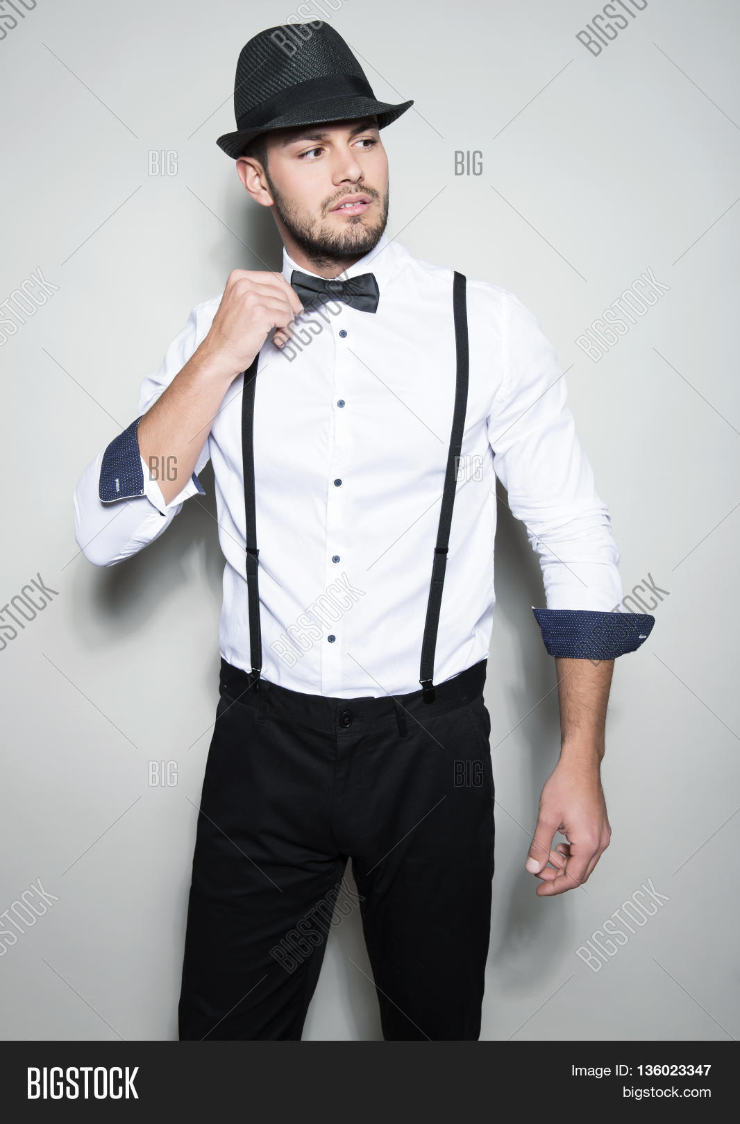 black shirt with white bow tie and white suspenders www