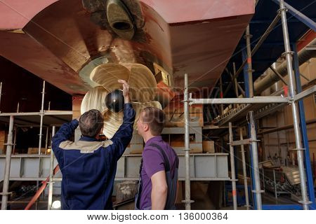 ST. PETERSBURG, RUSSIA - MAY 24, 2016: Workers at one of propellers of the passenger catamaran of the project 23290 at Sredne-Nevsky shipyard. The shipyard started producing such catamarans in 2013