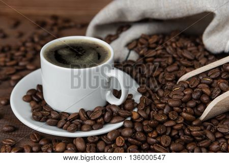 White porcelain cup of coffee on the background of coffee beans