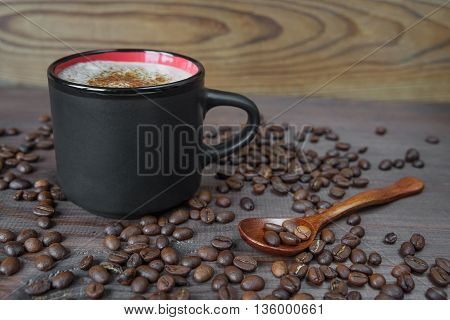 Black cup of coffee on the wooden background with coffee beans