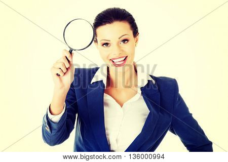 Young attractive business woman looking into a magnifying glass