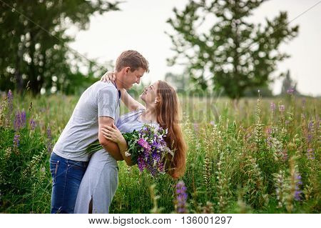 portrait of young stylish fashion couple in field looking on each other.