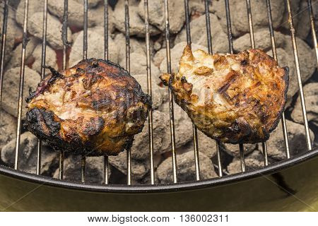 Chicken breasts cooking on a hot charcoal grill.