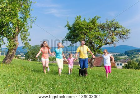 Father with children running on green meadow grass