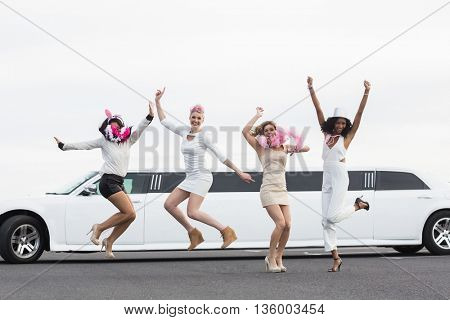 Happy friends jumping in front of a limousine on a night out
