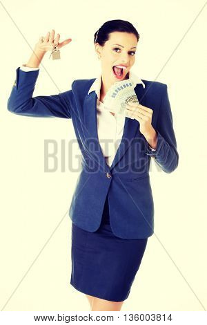 Beautiful young woman holding euro and house keys - real estate