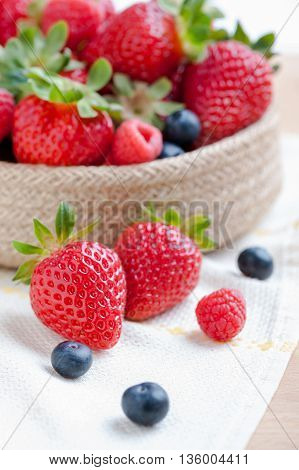 still life of strawberries and raspberries accompanied by berries