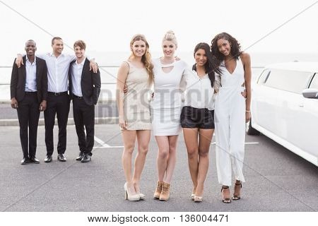 Well dressed people posing next to a limousine on a night out