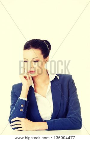 Pretty businesswoman sitting at the desk and thinking