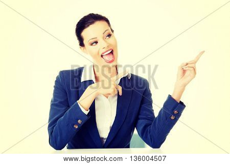 Businesswoman sitting at the desk and pointing on empty copy spa
