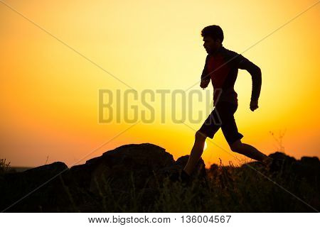 Young Sportsman Running on the Rocky Mountain Trail at Sunset. Active Lifestyle Concept