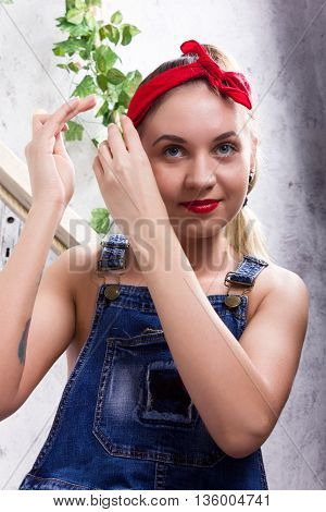 beautiful young woman in denim overalls and a bandana looking at the camera as the mirror, Chupa Chups licking and posing.