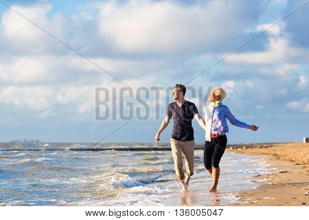 Couple enjoying romantic sunset at north sea beach