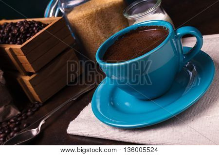 Cup of coffee and jute bags wooden containers filled with cofee beans on the rust background. Cane sugar. Low light.
