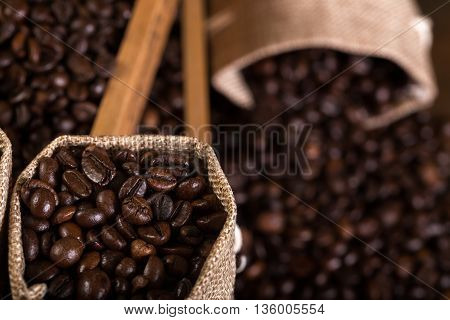 Jute bags and wooden containers filled with cofee beans on the rust background. Low light.