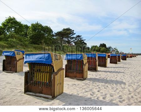 Scharbeutz, Germany - May 23, 2008: Beach with beach chairs along baltic sea coast trees in the background