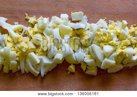 finely chopped boiled eggs in the middle of an old wooden cutting board close-up view from above
