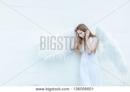 Angel girl with white wings standing near a white wall. She lowered her head down