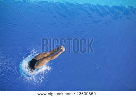 Female springboard diver diving into a swimming pool