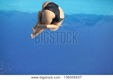 Lady springboard diver jumping into a swimming pool