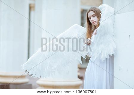 Girl with white wings wrapped in a wing and looking down