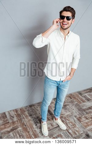 Full length portrait of a young happy man talking on the phone over gray background