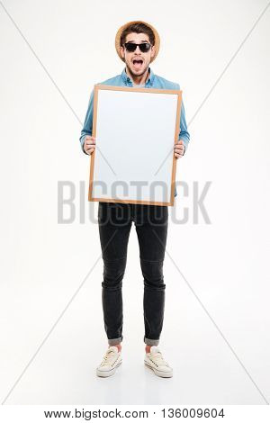 Amazed young man with mouth opened shouting and holding blank whiteboard over white background